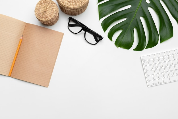 Workspace with keyboard, palm leaf and accessories. flat lay, top view copy space