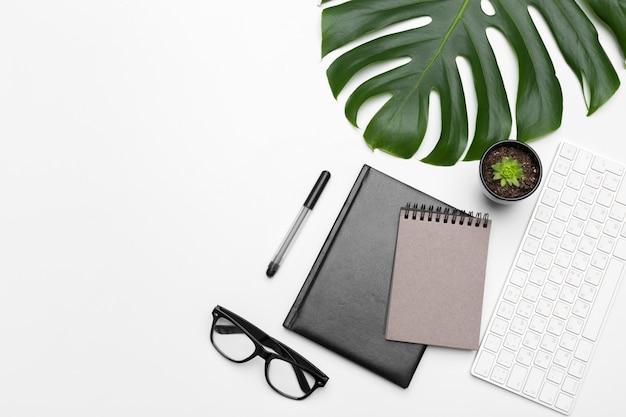 Рабочая область с клавиатурой, пальмовым листом и аксессуарами. плоская планировка, вид сверху копией пространства