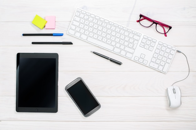 Workspace with keyboard, smartphone, tablet and office supplies on white