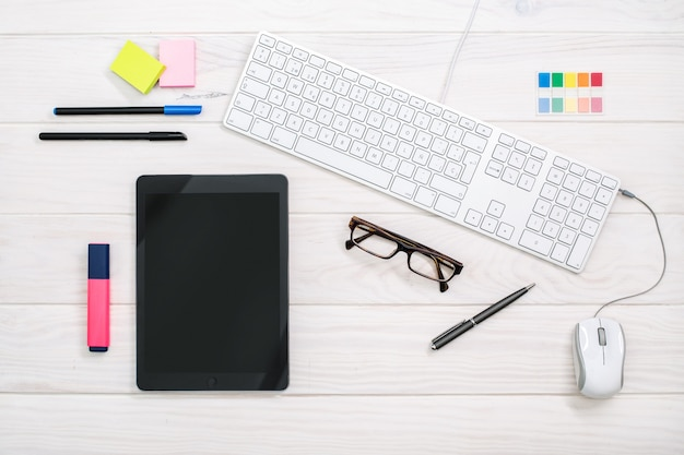 Workspace with keyboard, tablet and office supplies on white