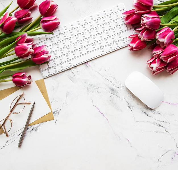 Workspace with keyboard and tulips