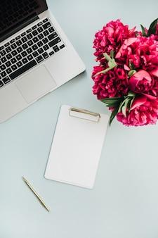 파란색 표면에 노트북, 빈 모형 클립 보드 및 분홍색 모란 꽃 꽃다발 작업 영역