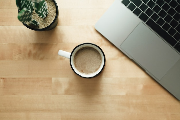 Workspace with laptop and coffee cup on wooden desk.