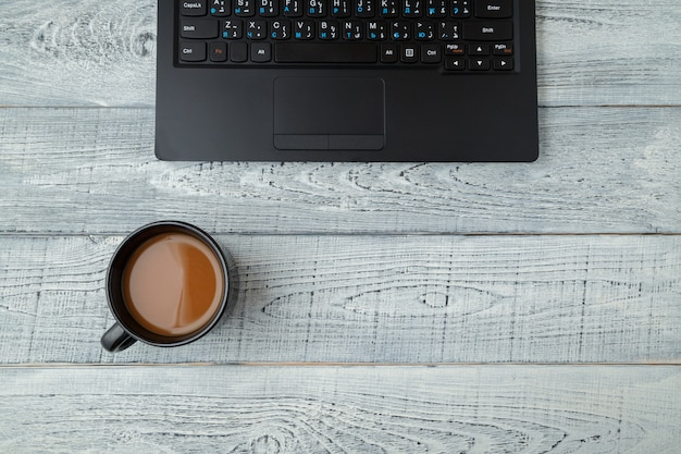 Workspace with laptop and coffee cup on wooden table