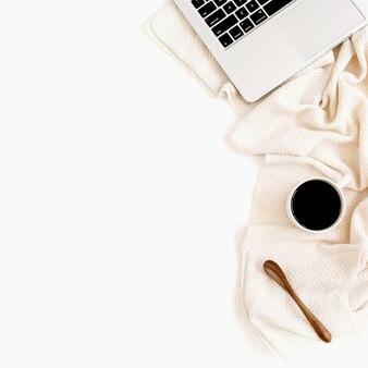 Рабочее пространство с ноутбуком, кофе, ложкой, белыми цветами и бежевой тканью на белой поверхности