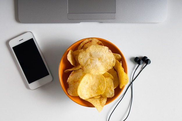 Workspace with laptop,crumpled paper and bowl of chips on wood table. bad habits concept