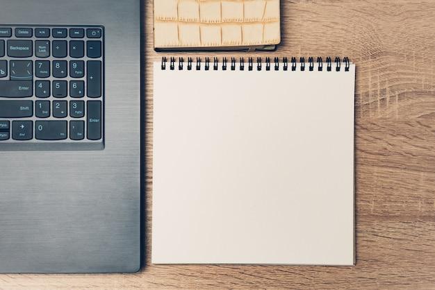 Рабочее пространство с ноутбуком клавиатура чистый лист бумаги блокнот