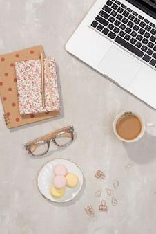 ラップトップ、ノートブック、グラス、一杯のコーヒー、トルコギキョウの花をグレーに持つワークスペース