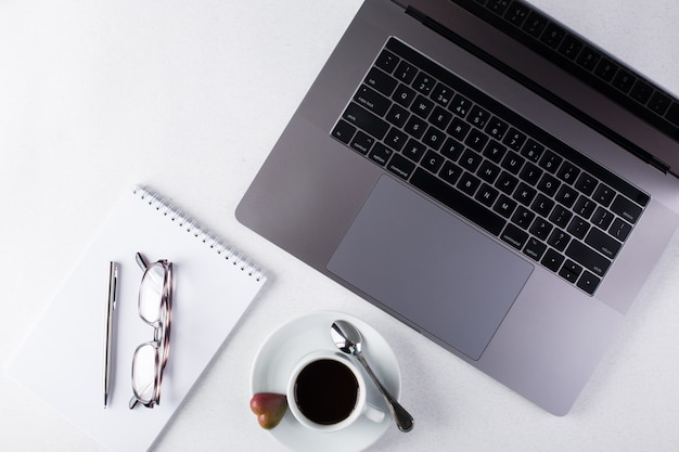 Workspace with laptop, notepad, tablet, glasses, cup of black coffee on a white background