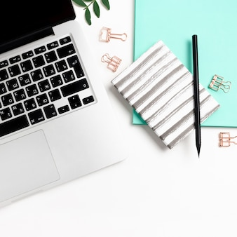 Workspace with laptop, notepads, pistachios branches, stationery on a white background