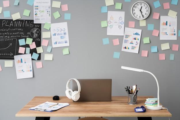 테이블에는 노트북이 있고 벽에는 스티커 메모가있는 작업 공간