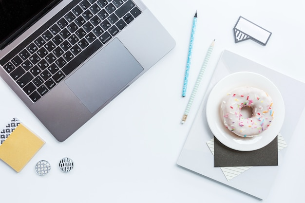 Workspace with laptop, pencil, notebook and donut on white background