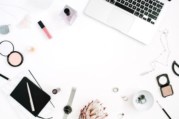 白い背景の上のラップトッププロテアフラワーノートブックとフェミニンなアクセサリーとワークスペースフラットレイトップビューホームオフィスデスク