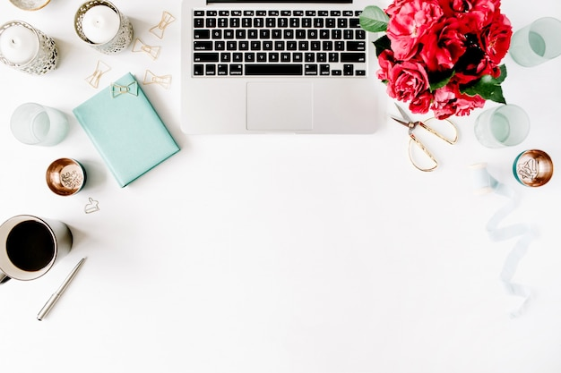 ノートパソコン、赤いバラの花束、ミント日記、コーヒーマグ、白地に金色のはさみを備えたワークスペース