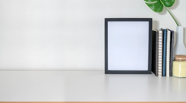 Workspace with mock up frame, office supplies and copy space on white top table and white wall.