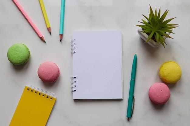 ノートブック、鉛筆、ペン、植物、マカロンのあるワークスペース。トレンディでカラフルなフェミニンな職場。