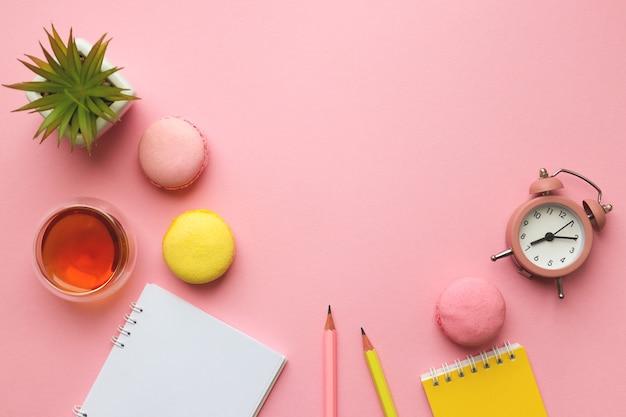 메모장, 연필, 알람 시계, 차 한잔, 마카롱 및 식물이있는 작업 공간