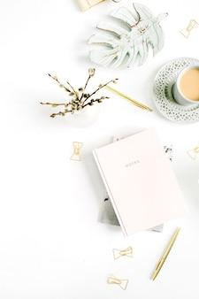 淡いパステル ピンクのノートと白い背景に装飾が施されたワークスペース。スタイリッシュなホームオフィスデスク