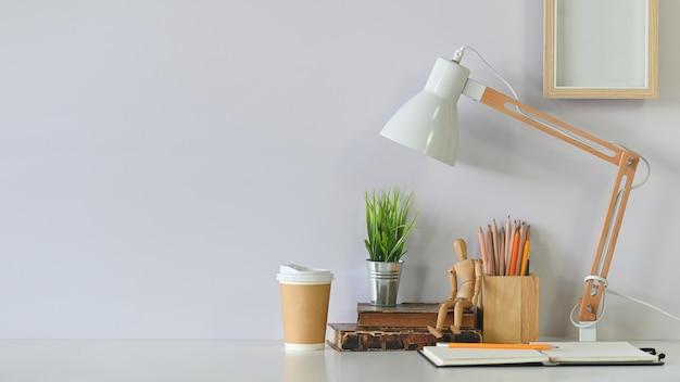 연필, 책, 커피, 사진 프레임 및 흰색 테이블에 램프 작업 영역.