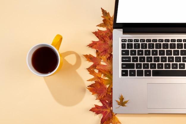 赤と黄色の落ち葉のあるワークスペースノートパソコンのお茶と影の居心地の良いオフィスベージュのデスク