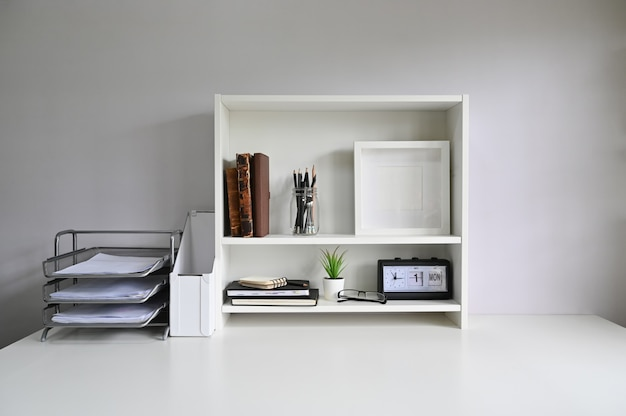Workspace with shelves and office supply on table.