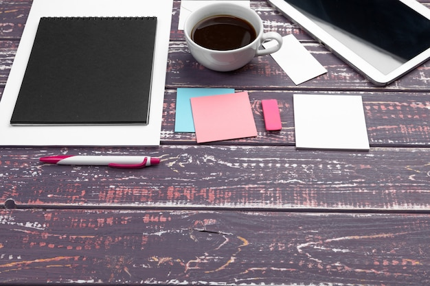 Workspace with stickers, notepad, pen and coffee