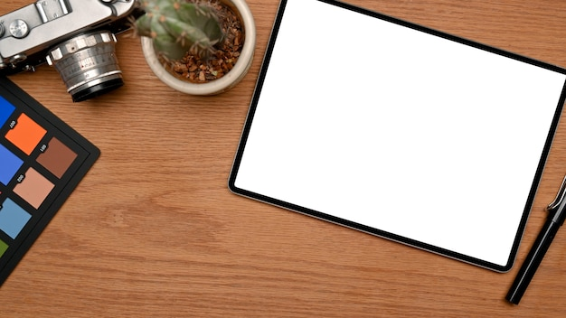 Workspace with tablet blank screen mockup colour checker and camera on wooden table top view