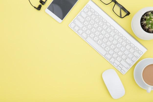 タブレット、キーボード、コーヒーカップ、眼鏡のあるワークスペースは、黄色の背景にスペースをコピーします。上面図。
