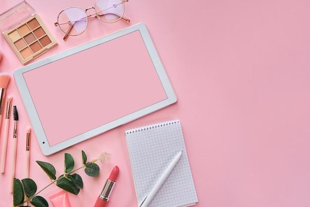 白いタブレット、メモ帳、メガネ、ペン、美容アクセサリー、キーボード、事務用品、緑の葉、ピンクの表面にコーヒーカップのあるワークスペース