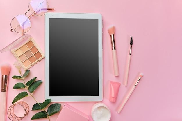 白いタブレット、メモ帳、メガネ、ペン、美容アクセサリー、キーボード、事務用品、ピンクの表面に緑の葉のあるワークスペース