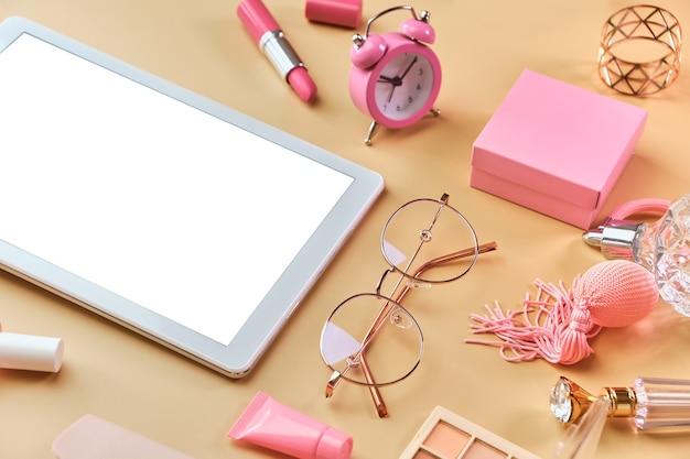 パステルベージュの表面に白いタブレット、メモ帳、メガネ、ペン、美容アクセサリーを備えたワークスペース