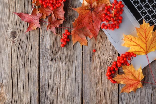 黄色と赤のカエデの葉を持つワークスペース。ラップトップ、灰色の木製の背景に落ち葉でデスクトップ