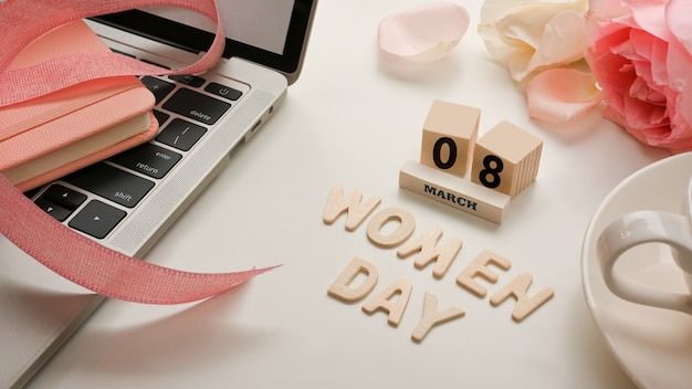 Workspace in women's day concept with laptop, flowers, coffee cup and message on white table