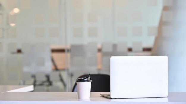 Портативный компьютер workspace и бумажный стаканчик кофе на фронте таблицы конференц-зала.