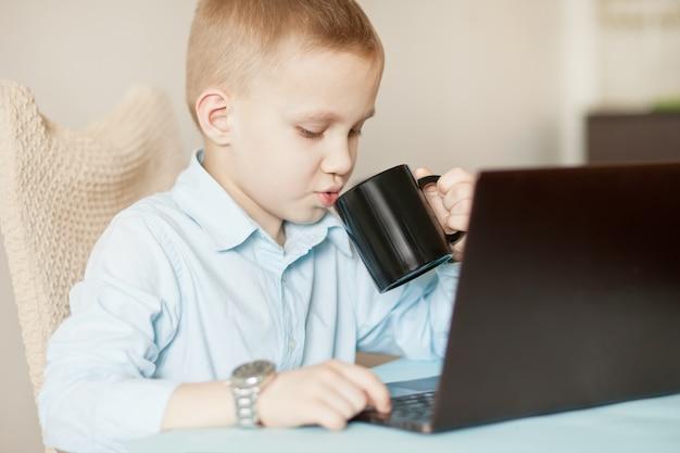 .workspaceオフィスデスクとラップトップ。テーブルに座って、コーヒーのマグカップを飲むビジネス少年。子供のオンライン学習。オンライン教育の遠隔学習。