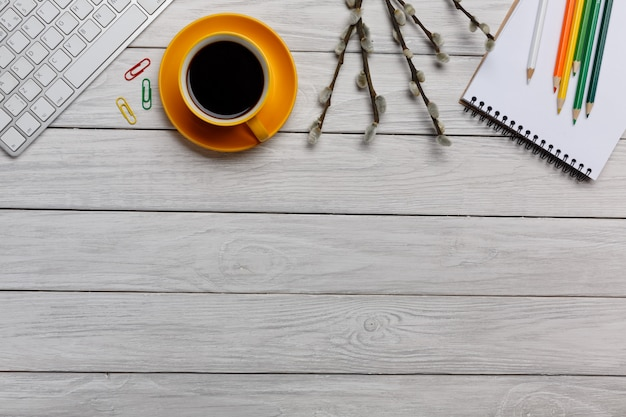Worktable white yellow cup of coffee pencils and notepad keyboard top view