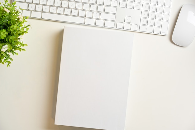 Worktable with white blank book cover mockup keyboardon white background top view