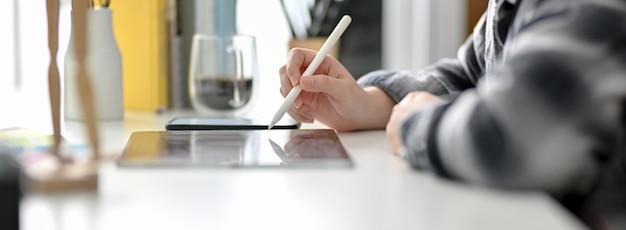 Взгляд со стороны женского график-дизайнера работая на цифровой таблетке на белом worktable