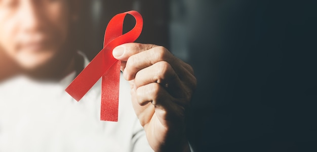 World aids day awareness ribbon, female hands holding red ribbon