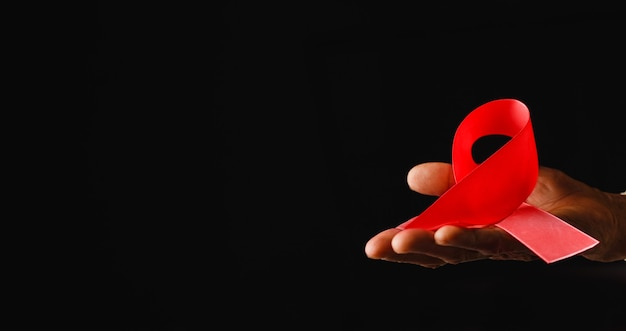 Лента осведомленности всемирного дня борьбы со спидом, старые женские руки держат красную ленту