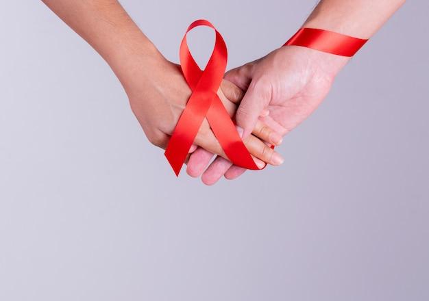 Международный день борьбы со спидом. мужчина и женщина держатся за руки вместе со спидом красной лентой