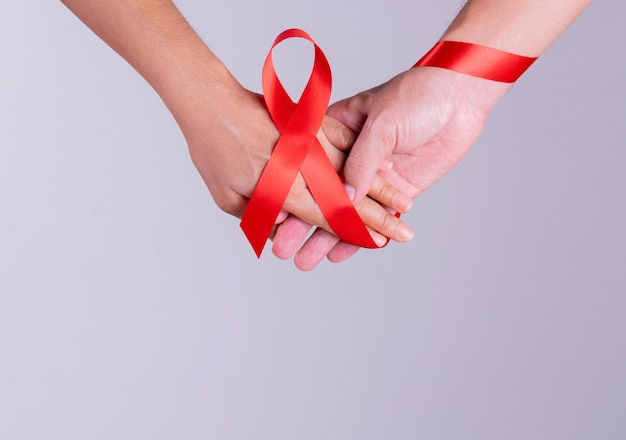World aids day. man and woman holding hands together with aids red ribbon