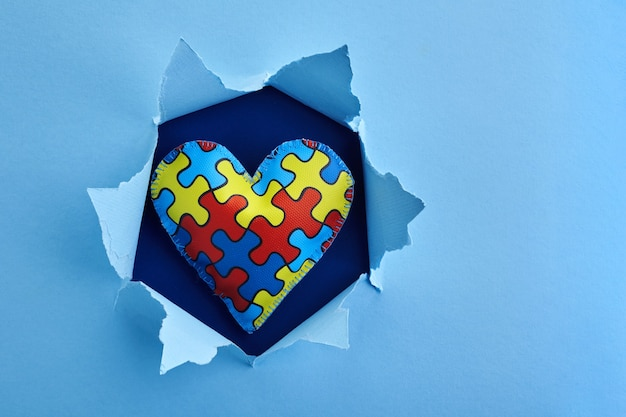 World autism awareness, concept with puzzle or jigsaw pattern on heart in paper cut hole