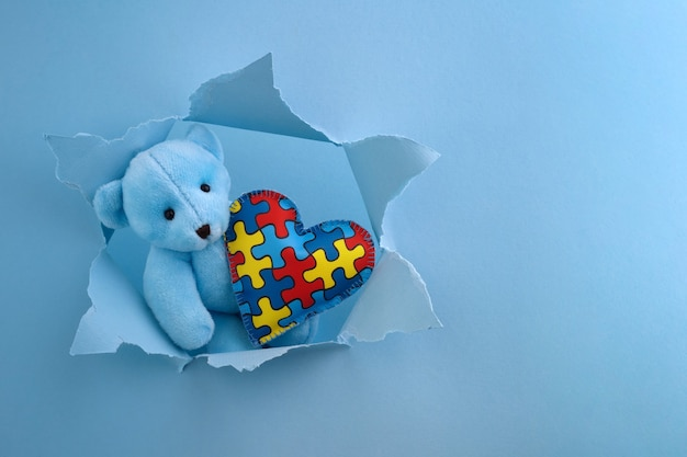 World autism awareness, concept with teddy bear holding puzzle or jigsaw pattern on heart in papaer cut hole