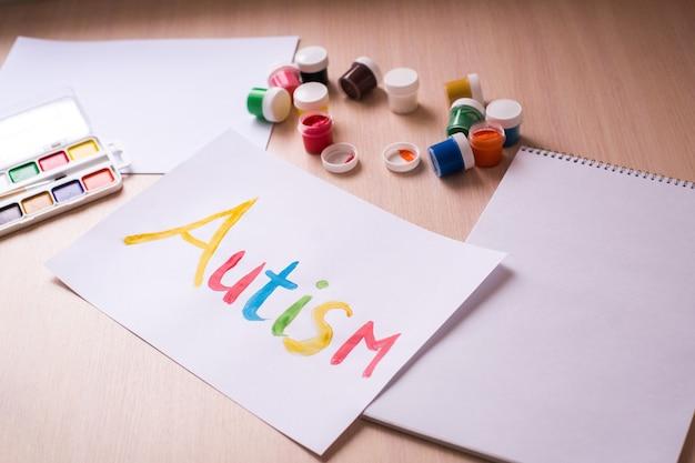 世界自閉症啓発デーのコンセプト。青い背景にハートと紙の手。自閉症スペクトラム障害(asd)。