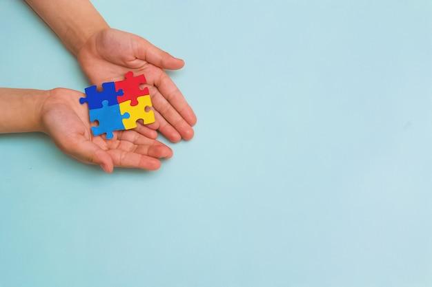 世界自閉症啓発デー青い背景にカラフルなパズルを持っている小さな子供の手