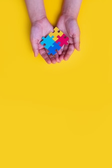 世界自閉症啓発デー黄色の背景にカラフルなパズルを持っている小さな子供の手
