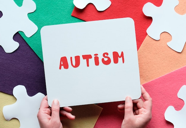 World autism awareness day. jigsaw puzzle on felt. hands hold cardboard placard with text autism..