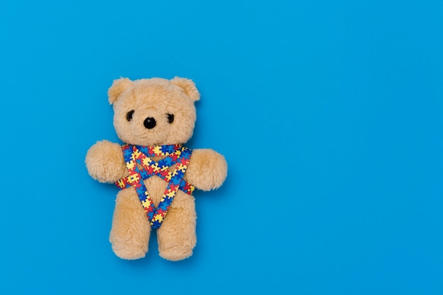 World autism awareness day, mental health care concept with teddy bear and ribbon puzzle pattern