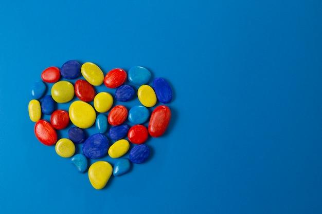 世界自閉症啓発デーのシンボル。塗装された小石で作られたハート Premium写真